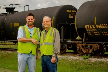 Paducah Area Community Reuse Organization Executive Director Scott Darnell, left, and EM Paducah Site strategic planner Buz Smith stand in front of tank cars at the site.