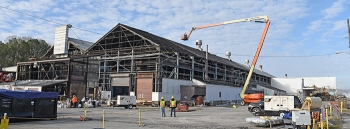 Workers take asbestos-containing panels off the K-1037 Building as the demolition project commences.