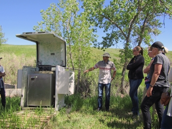 Subject matter expert, George Squibb, LM support contractor, explains surface water monitoring station during the Rocky Flats Stewardship Council tour.