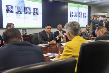 Honorable Director Campos at the conference table speaking with participants