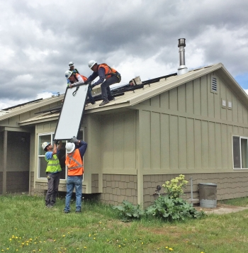 Team of people installing solar panels on a house.