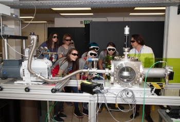 Laboratory researcher Adrianna Reyes-Newell (right) shows camp participants how laser-induced breakdown spectroscopy works. The ChemCam instrument on the Curiosity rover uses this technology to investigate the composition of Martian rocks.