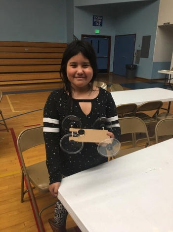 "Older students at Lapwai Elementary School's family STEM night built cars with retractable badge clip ""motors."""
