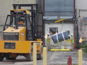 Workers remove a 900-pound lift bag of asbestos material from the Main Plant Process Building at EM's West Valley Demonstration Project. The bag was carried out of the facility on a conveyor system created by employees at the site.