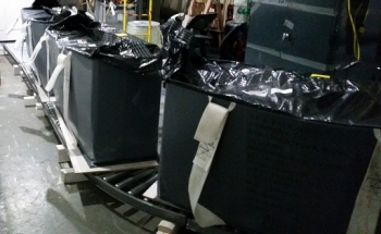 Three 900-pound lift bags filled with asbestos material sit on a conveyor system designed by workers at EM's West Valley Demonstration Project.