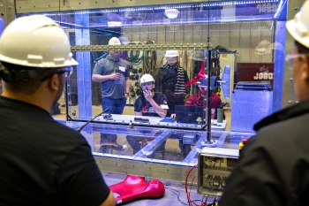 Three students wearing safety gear are visible through a glass enclosure with a small-scale wind turbine, while two people in the foreground take measurements.