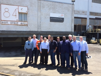 11 men standing in front of the ArcelorMittal building