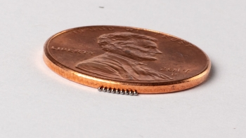 Closeup photo of a penny next to MiniFuel targets that look like tiny beads, to show scale.