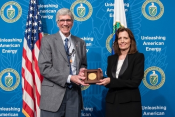 Dr. Charles Verdon, NNSA's Deputy Administrator for Defense Programs, presents Dr. Kathi Alexander with the NNSA gold seal for her exceptional service for more than 30 years.