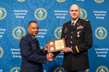Col Michael Clancy, former Executive Director of Major Modernization Programs, present Lt. Col. Greg Schwarz with a plaque in recognition of his 23 years of exception service in the U.S. Army.