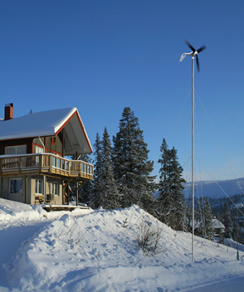small wind turbine outside of a snowy cabin on a mountain.