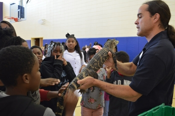 Sean Poppy, outreach coordinator for the University of Georgia's Savannah River Ecology Laboratory outreach program, shows a juvenile alligator to students at Blakeney Elementary School in Waynesboro, Georgia.