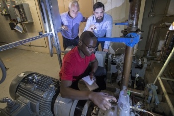 Joseph Tuozzolo (left) and J.T. Benante (right), provide guidance to intern Steven Snell, who is checking the status of a pump that is part of the cooling system at the AGS.