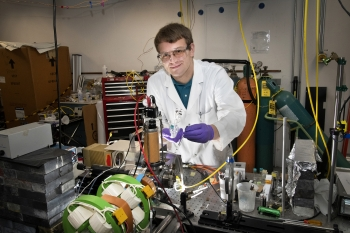 """intern Christopher Hayes in Brookhaven Lab's Chemistry Division, where he is studying an organic polymer """"doped"""" with clusters of the element boron to understand the energetics of electric charge transfer and escape that are relevant to solar cells."""