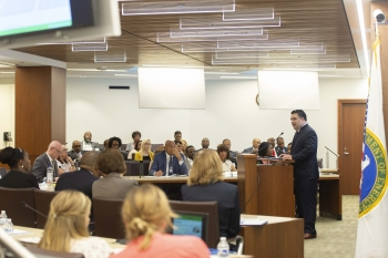 The Honorable James E Campos stands at a podium speaking to attendees.