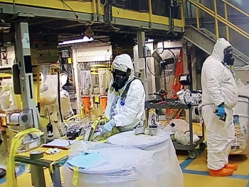 EM workers, donning required personal protective equipment, safely condition and repackage remaining waste in the Accelerated Retrieval Project V facility at DOE's Idaho National Laboratory Site.
