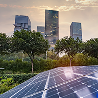 Solar panels in the foreground with a city skyline in the background on a partially cloudy day.