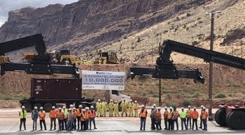 EM Moab Uranium Mill Tailings Remedial Action Project employees gather around project equipment after loading the 10 millionth ton of uranium mill tailings into a container to be shipped by train to the Crescent Junction disposal cell.