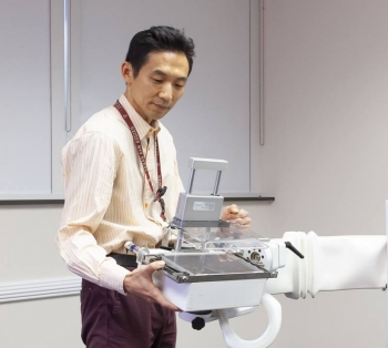 Seung Joon Lee holds the variable angle slant hole collimator. This device can help a breast molecular imaging system get six times better contrast of cancer lesions, providing the same or better image quality while potentially halving the radiation dose.