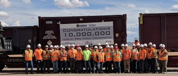 Employees at the Crescent Junction disposal cell site come together to mark the milestone as they await the train carrying the 10 millionth ton from the Moab Uranium Mill Tailings Remedial Action Project.