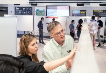Physicist Eric Fredrickson looks at a student's poster during the poster session.