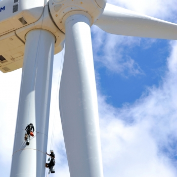 A worker climbing a wind tower.