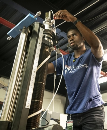 Promise Adebayo-Ige calibrates the device before experiments begin.