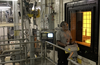 An operator at the Defense Waste Processing Facility maneuvers a canister inside the DWPF canyon via remote controls. All radioactive operations inside DWPF are conducted remotely.