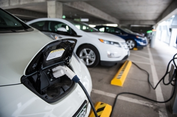 The front of an electric vehicle with a plug inserted into the battery at a charging station in the NREL garage.