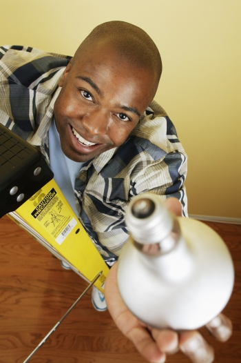 A young man holds a lightbulb up in the air.