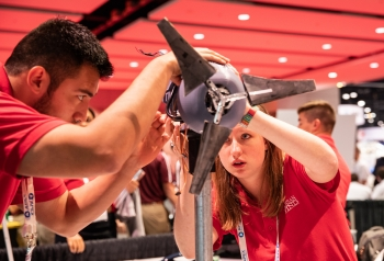 Two students wearing school shirts adjust the nacelle on a model wind turbine.