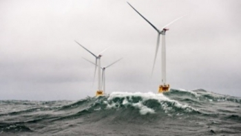 three offshore wind turbines at sea against a grey sky and choppy waves.
