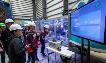 participants in the collegiate wind competition watch their turbine test on a screen.