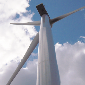 View from below of a wind turbine against a blue sky with some clouds.