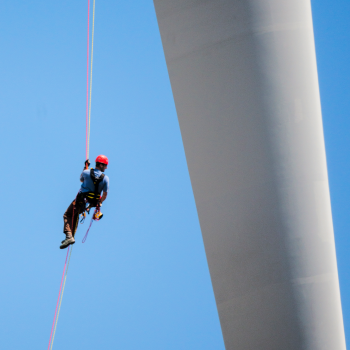 Worker hanging from cable between wind turbine rotor and tower with blue sky behind him.
