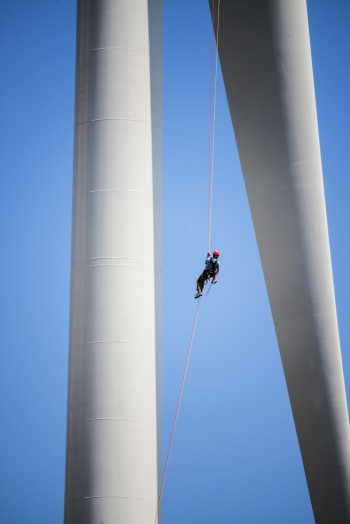 Photo of a wind turbine technician dangling from a rope between two wind turbine blades.
