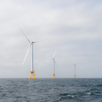 Photo of 4 wind turbines on orange platforms in the middle of ocean.