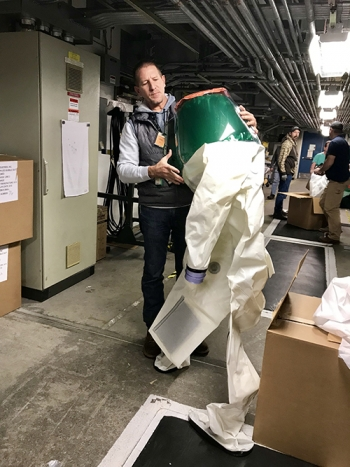 "Former Advanced Mixed Waste Treatment Project (AMWTP) employee Chad Jardine holds a ""bubble suit,"" a critical piece of personal protective equipment for workers who conduct maintenance in AMWTP's boxlines."