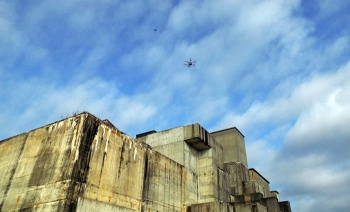A small aerial drone with a high-resolution camera hovers above a larger drone that identifies where to spray herbicide on the rooftop of a closed reactor building.