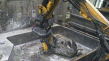 A robotic arm resizes a metal tank in one of the Advanced Mixed Waste Treatment Project's boxlines.