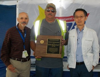 Dae Chung, far right, EM Deputy Assistant Secretary for Safety, Security, and Quality Assurance, presents the DOE Voluntary Protection Program Star of Excellence award to John Rendall.