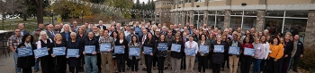 Participants in DOE's recent safety culture workshop in Idaho Falls gather for a photo, with some attendees holding safety messages.