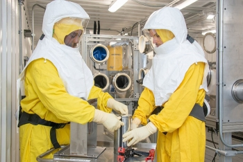 Savannah River Site radiation protection employees don protective equipment while working in a glovebox. Gloveboxes are structures with ports containing gloves that allow waste handlers to safely work with radioactive material.