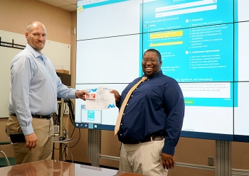 Savannah River Remediation (SRR) Process Applications Engineer Eric Dantzler, right, receives a gift card from his co-worker Jason Hargrave. Dantzler was nominated for the reward through SRR's new RAVE (Recognizing Achievement of Values and Expectations)