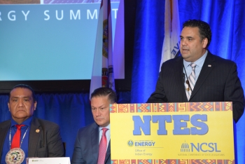 Honorable James E. Campos speaks at a podium labeled NTES. Kevin Frost and another man listen attentively.