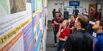 Students wearing shirts from different universities look at posters at the 2019 Collegiate Wind Competition.