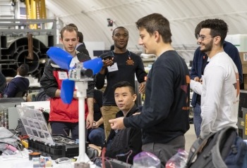 A group of students smile at a model wind turbine at the 2019 Collegiate Wind Competition.