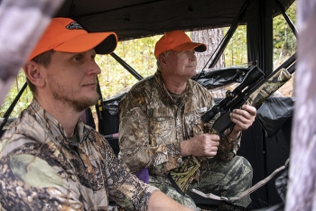 Robert Starnes, right, a U.S. Army veteran, waits with his son, Rob Starnes, as they look and listen for wild hogs and deer during the 20th annual deer hunt at the Savannah River Site.
