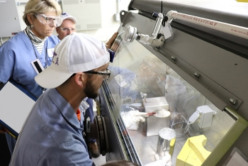 DOE Oak Ridge Office of Environmental Management fissionable material handlers open a canister containing Uranium-233 to begin the extraction process.
