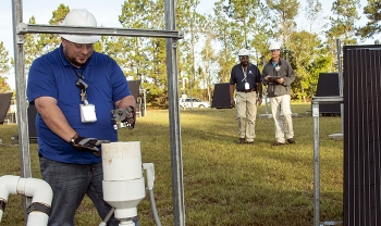 Savannah River Nuclear Solutions (SRNS) Mechanic Thad Ashely, foreground, checks components of a soil vapor extraction unit, as SRNS engineers Joao Cardoso-Neto, background, left, and John Bradley inspect solar panels.